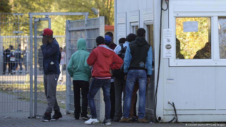 چند پناهجو در نزدیک در ورودی مرکز ثبت نام پناهجویان در نزدیکی مونیخ؛ عکس از آرشیو (اکتبر ۲۰۱۴)