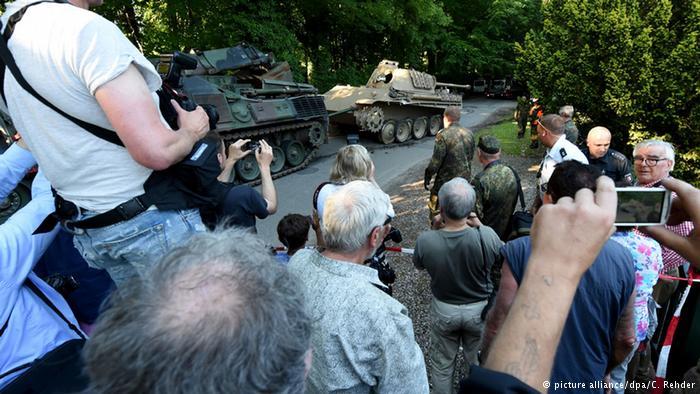 مردم محلی که انتقال سلاحهای کشفشده را تماشا میکنند.