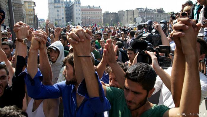 پناهجویان زنجیره انسانی تشکیل داده و شعار میدهند-میخواهیم از اینجا برویم.
