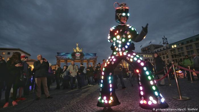 """مردی با کلت و شلوار نورانی مقابل دروازه براندنبورگ برلین در """"جشنواره نور."""""""